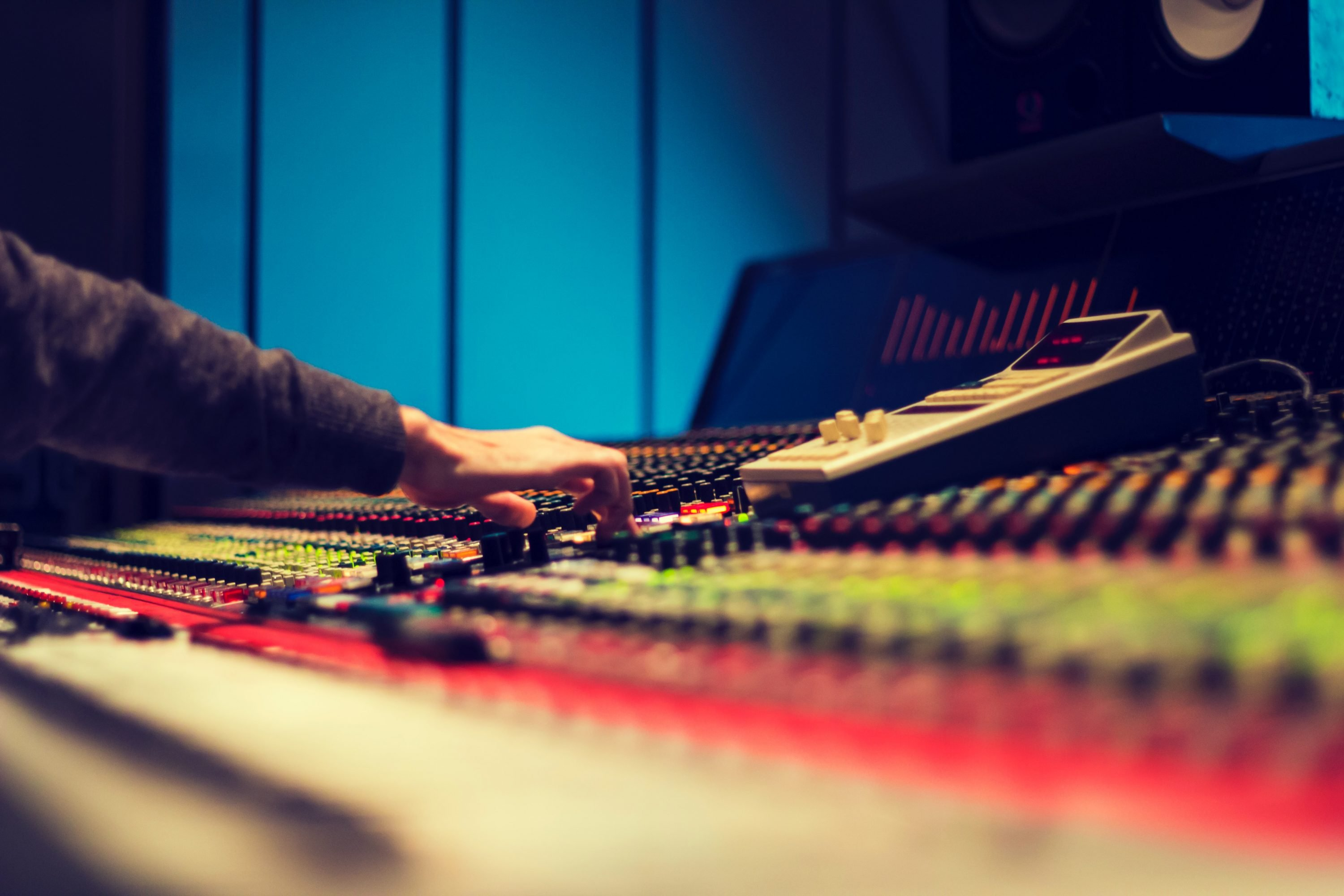 Close up image of sound engineer's hands moving dials on mixing and mastering console.